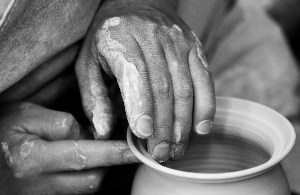 Eine Hand an der Töpferscheibe