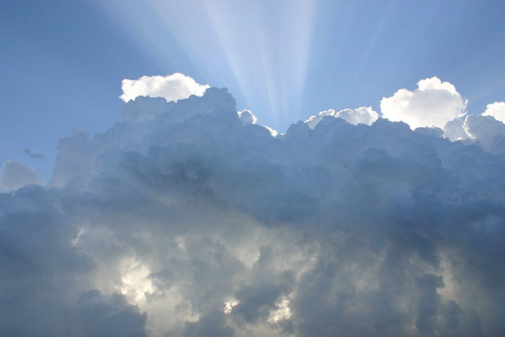 Ein blauer Himmel mit Wolken und Sonnenstrahlen