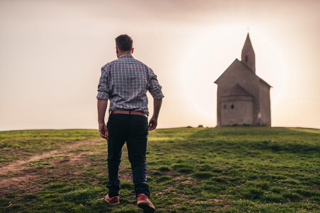 Mann geht über Wiese auf Kirche zu