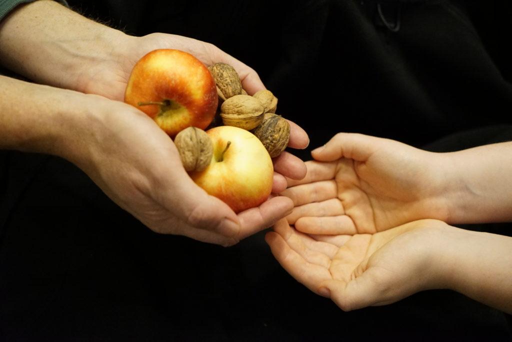 Zwei Händepaare, die eine gibt Äpfel und Nüsse in die andere.