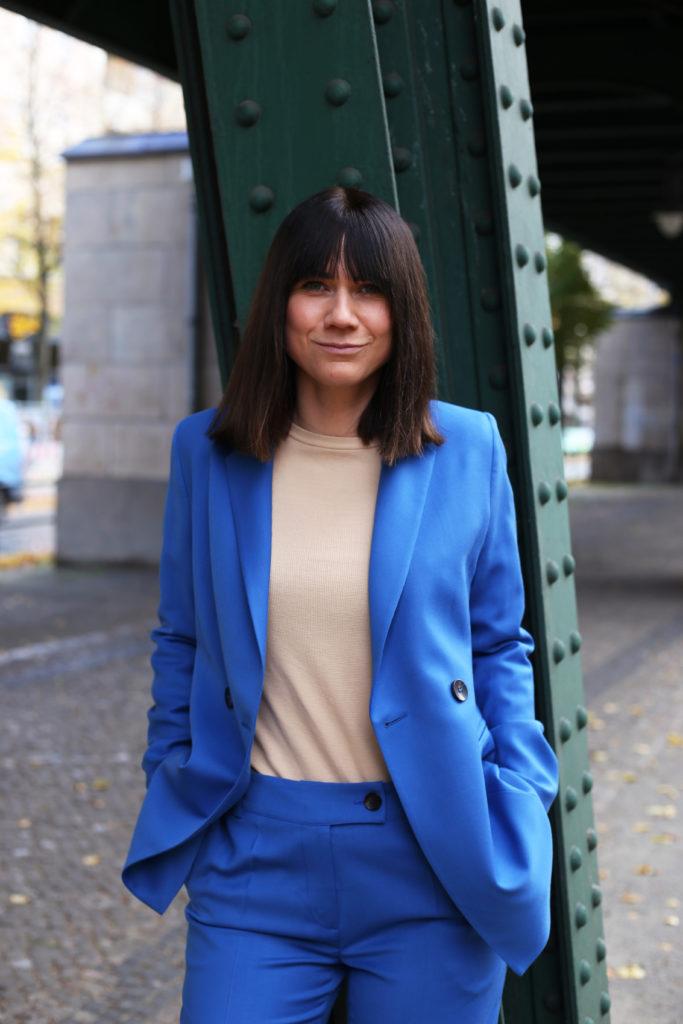Eine Frau im blauen Anzug vor einer Metallsäule