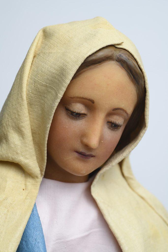Eine Marienfigur: Maria schaut nach unten, sie trägt ein weißes Gewand. ,