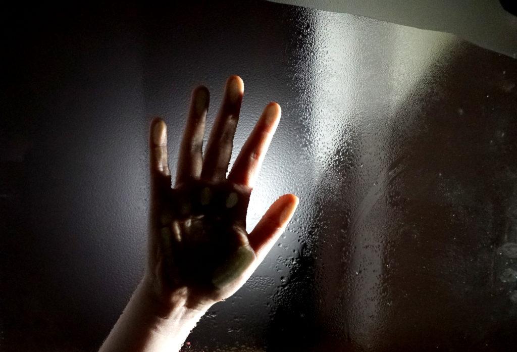 Eine Hand an einer Glasscheibe