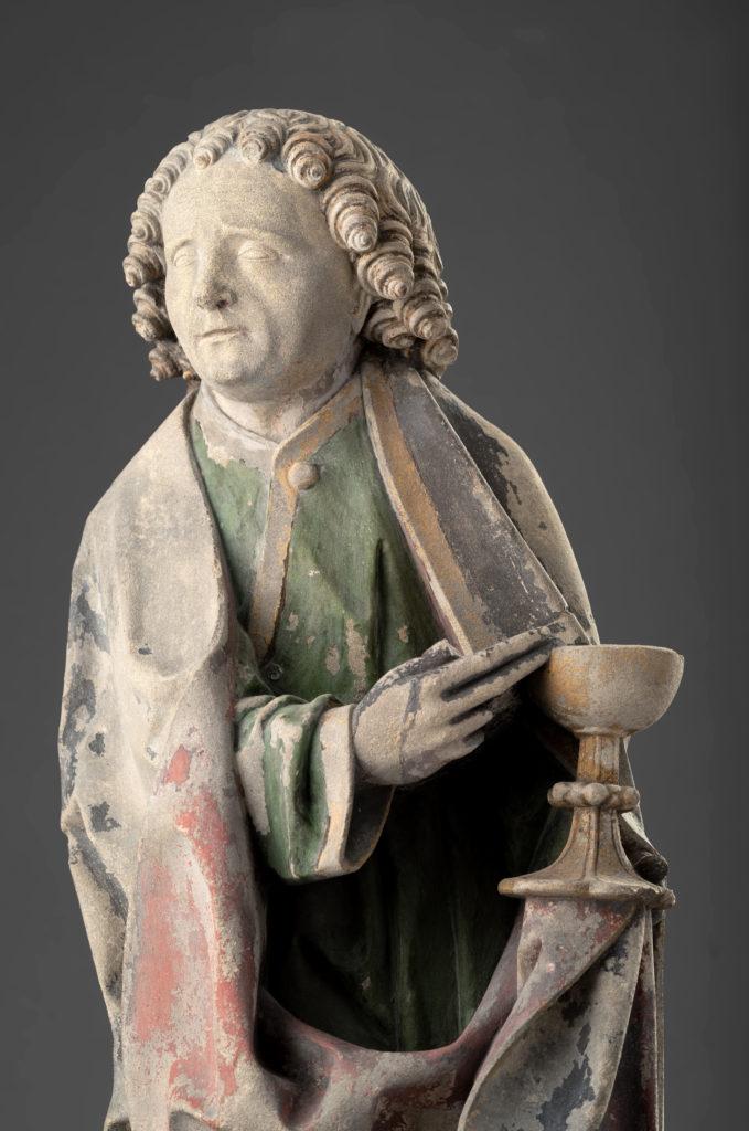 Die Skulptur zeigt einen Mann mit einem Kelch in der Hand