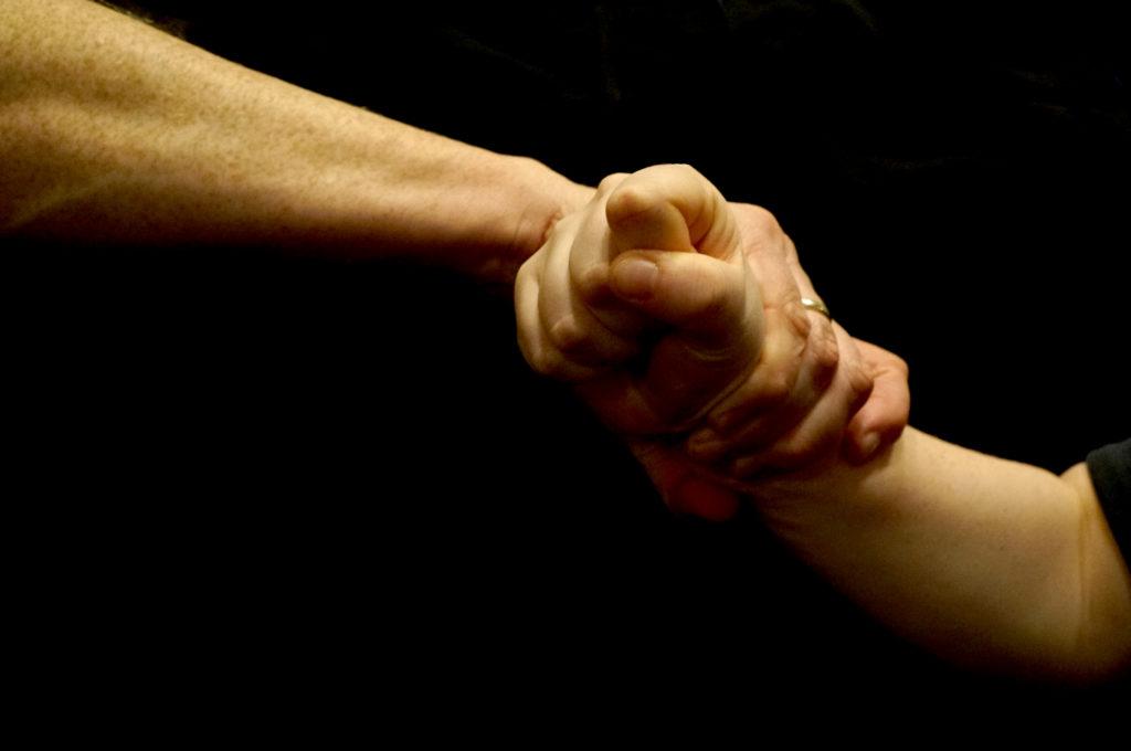 Zwei Hände, die sich festhalten.
