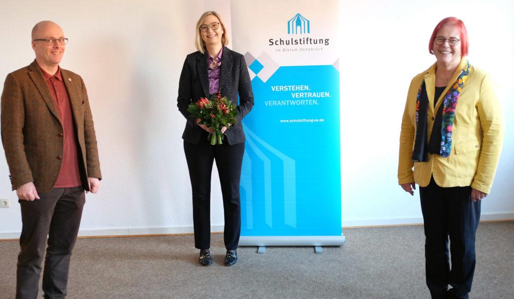 Zwei Frauen und ein Mann stehen im Raum, dahinter das Logo der Schulstiftung.