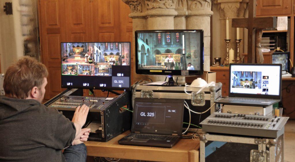 Ein Mann sitzt in der Sakristei des Osnabrücker Doms vor vielen Bildschirmen.