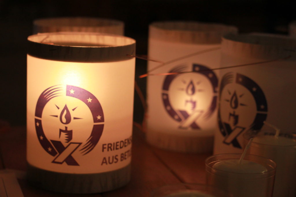 Eine kleine Kerze in einer Laterne leuchtet.