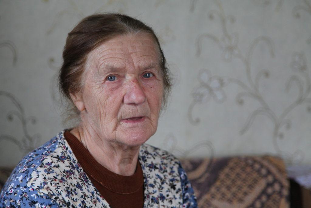 Eine alte Frau sitzt auf ihrem Sofa und schaut in die Kamera.