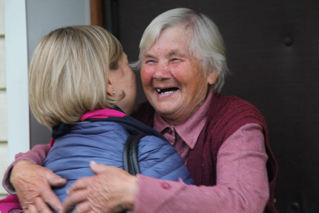 Zwei Frauen, eine jüngere, eine ältere, umarmen sich.