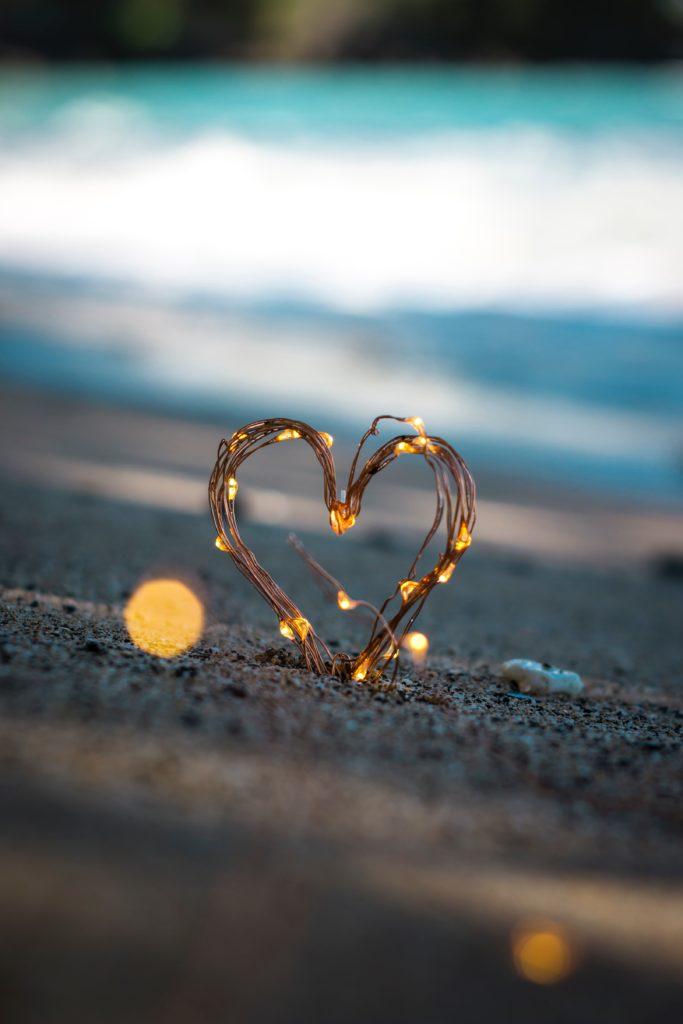 Herz aus Lichterkette im Sand