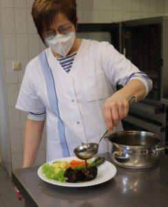 Maria Huesmann vom Jugendkloster Ahmsen richtet Rinderrouladen auf einem Teller an und begießt sie mit brauner Soße.
