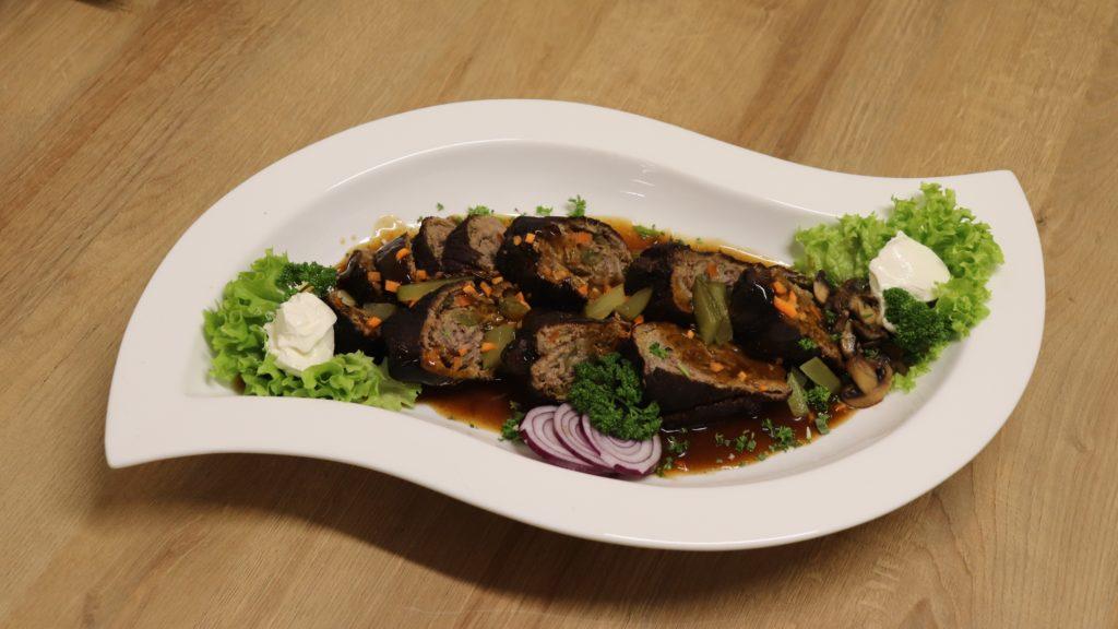 Rinderrouladen traditioneller Art aufgeschnitten und angerichtet mit brauner Soße und Salatgarnitur