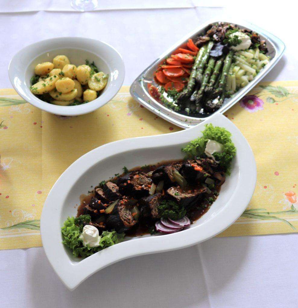 Rinderrouladen traditioneller Art, angerichtet in einer weißen Schale, daneben Kartoffeln, grüner Spargel und Wurzelgemüse als Beilage.
