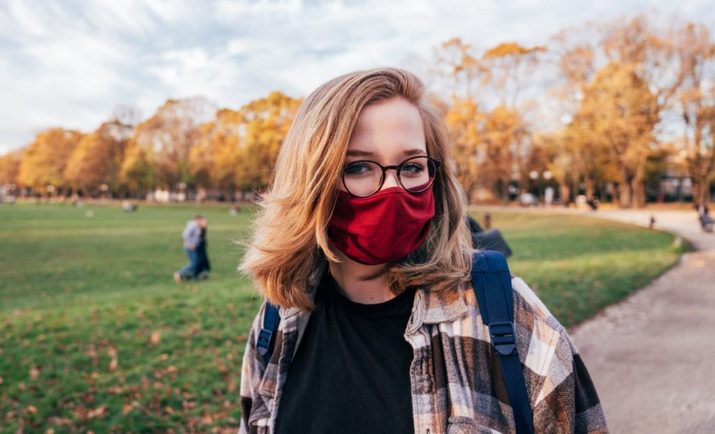 Eine Frau im Jacket mit Brille steht in einem Park