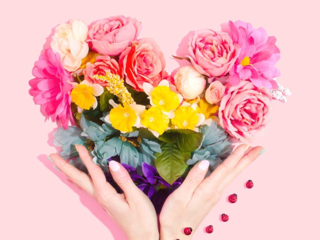 Hände halten bunten Blumenstrauß