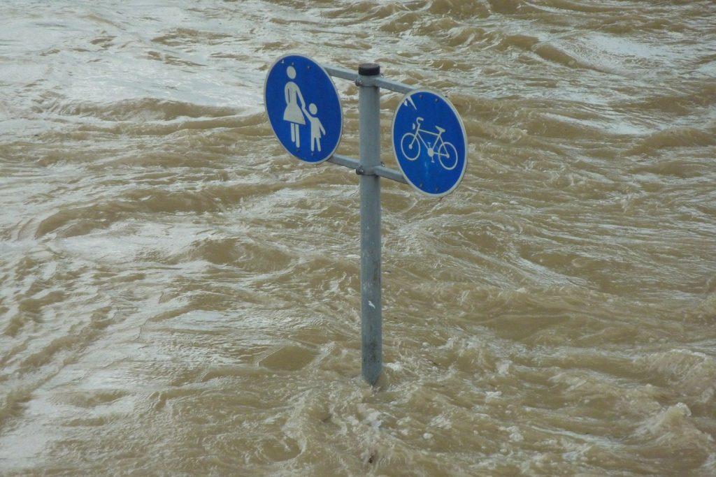 Straßenschild im Hochwasser