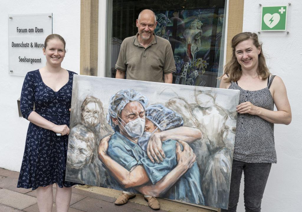 Drei Menschen tragen Bild, auf dem sich zei Menschen umarmen