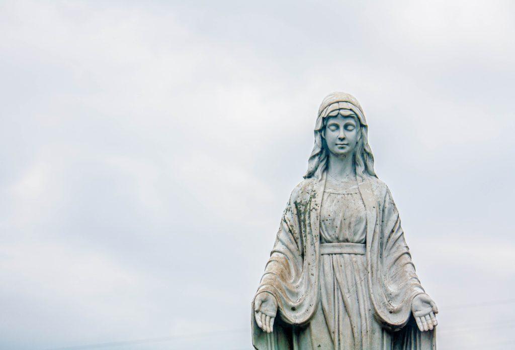 Eine Marienstatue vor bewölktem Himmel