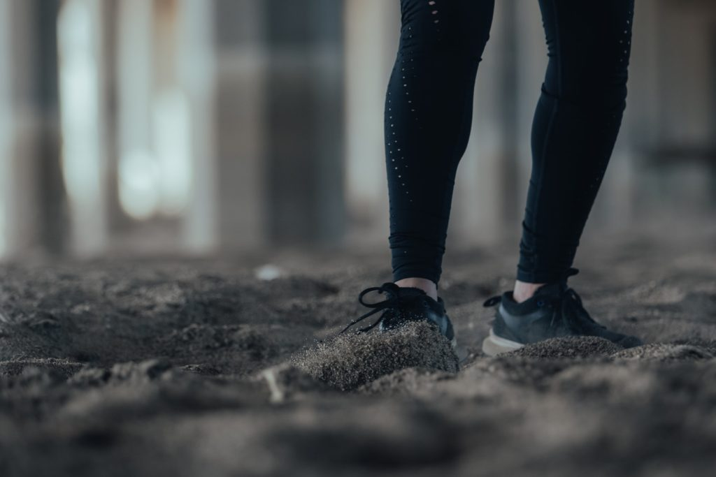 person in black pants and black shoes standing on gray concrete floor